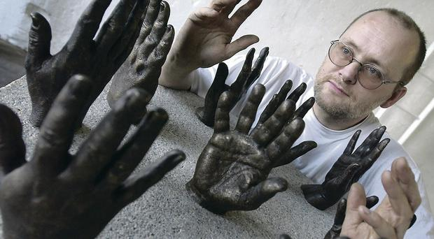 Raymond Watson with a piece called Hands of History, which depicts the bronze casts of the hands of those who negotiated Good Friday Agreement