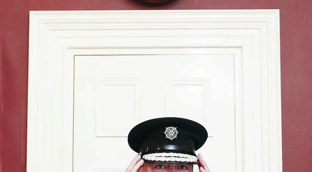 Chief Constable Matt Baggott is asked to straighten his peaked cap and look serious for the camera