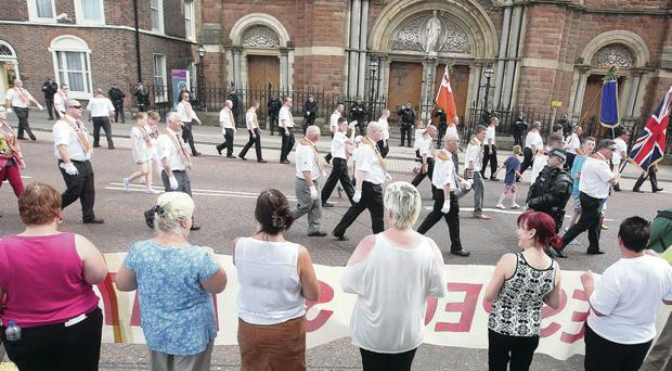 Marching past: The Twelfth parade passes St Patrick's Catholic Church in Belfast