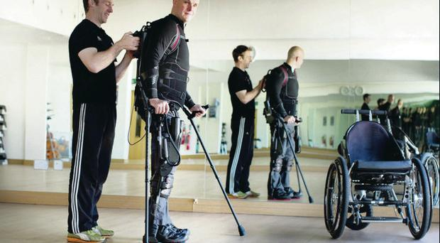 True champion: Mark Pollock and (left) with his girlfriend Simone George pressEyeFighting back: Mark with his robotic legs helped by trainer and South Pole teammate Simon O'Donnell and (below) in hospital after falling out of a window and breaking his back in 2010 David Conachy