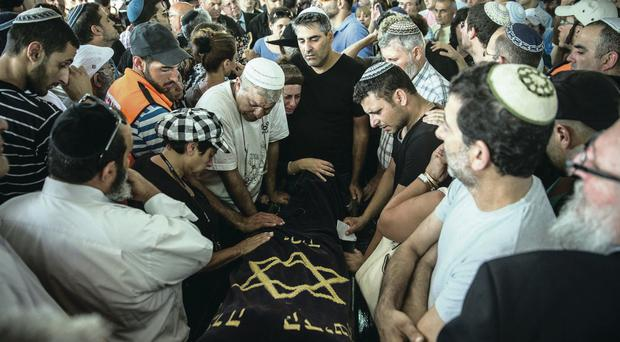 Troubled times: mourners weep during the funeral of Dror Khenin