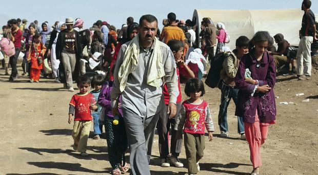 Under threat: Displaced Iraqis arrive at a refugee camp