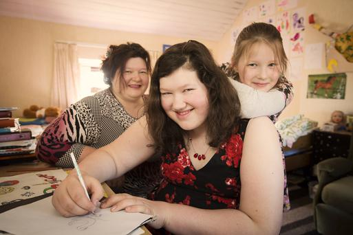 Drawing strength: budding artist Sara Gulbe with mum Anita and sister Laura