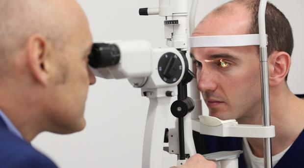 First-class facility: Colin Coleman's eyes are examined by Professor Johnny Moore