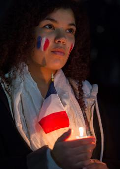 Showing solidarity: a French woman taking part in a candlelit vigil