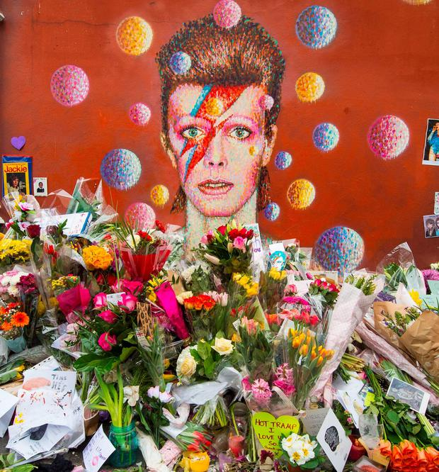 Mourning fans heaped flowers beside a mural of iconic rock musician David Bowie in Brixton, south London on Tuesday