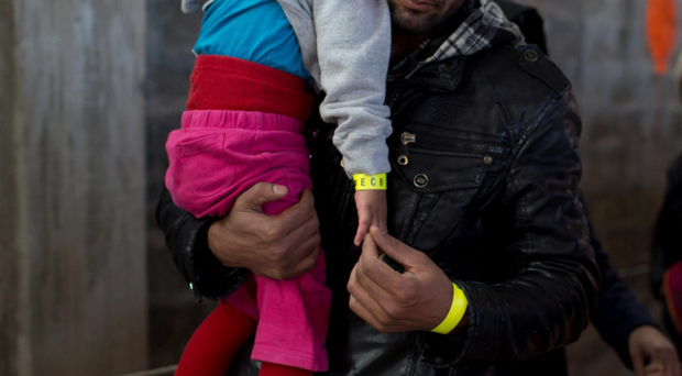 Stand out: a refugee and his daughter wearing wristbands