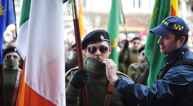 A member of the Garda exposes the face of a masked member of a republican colour party on the centenary of the Easter Rising in Dublin on Monday