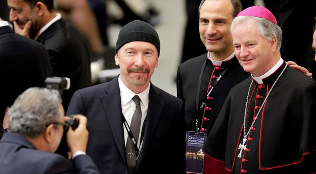 Top cap: The Edge at the Vatican last month with Irish Bishop Paul Tighe (right)