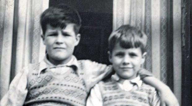 So close: George Larmour sits smiling in a childhood photograph beside John