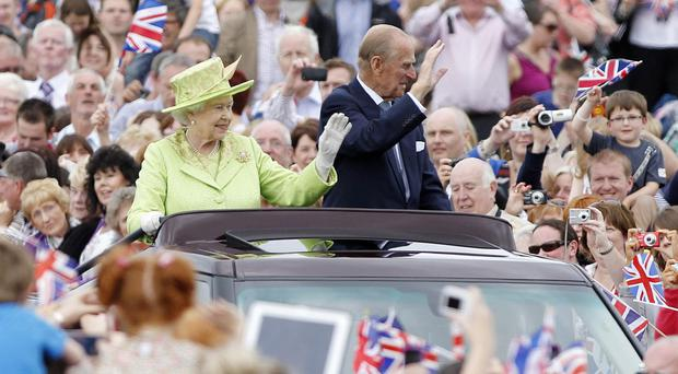 Enduring contribution: the Queen and the Duke of Edinburgh tour the grounds of Stormont in Belfast back in 2012