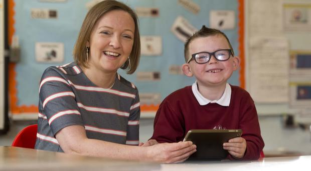 Acting principal Emma Quinn helps Clarke McMullan (6) use a school iPad at Rathcoole Primary School, Newtownabbey