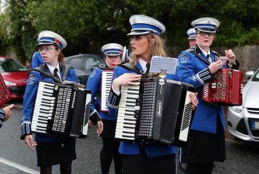 Drum Accordion Band members, turned out smartly in their uniforms, lead the procession of local Orange lodges