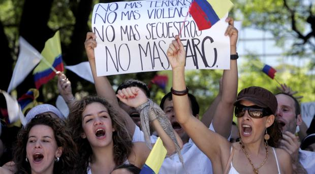 Troubled land: Colombian citizens hold up a sign that reads 'No more terrorism, no more violence, no more kidnapping, no more FARC'