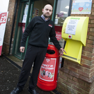 Under attack: Richard Campbell, proprietor, Spar shop in Londonderry, beside the damaged defibrillator box