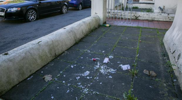 The area is littered with empty bottles, broken glass and discarded furniture