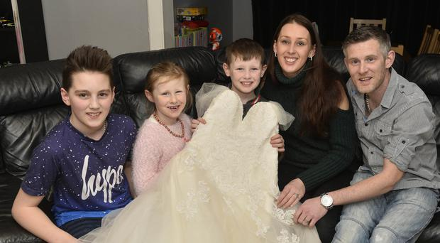 Kelly, her husband Jordan McGeown and children (from left) Jack, Georgia and Alexander with the wedding dress