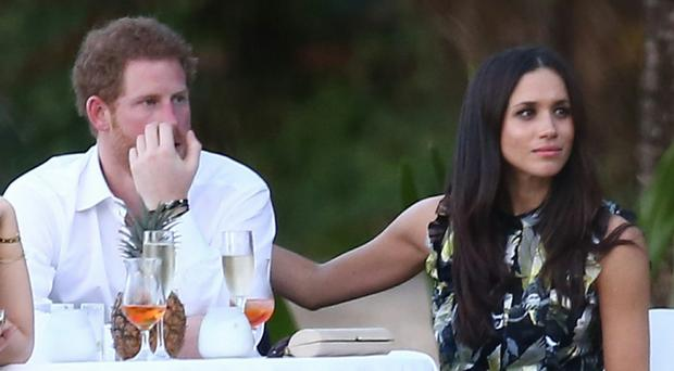 Good cheer: Prince Harry with his girlfriend, Meghan Markle