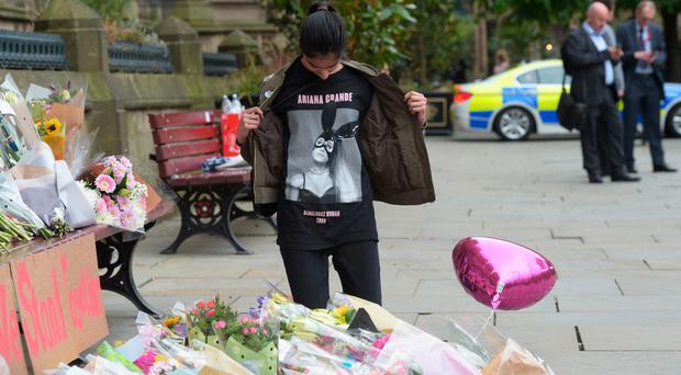 Star power: a young teenager wears an Ariana Grande T-shirt as she looks at flowers outside Manchester Town Hall in Manchester