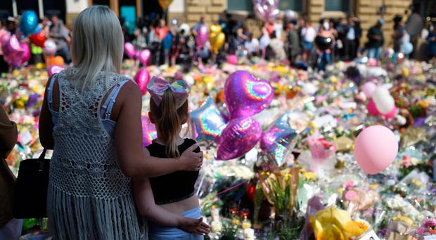 Poignant scene: a mother and child view the flowers and messages of support at St Ann's Square in Manchester
