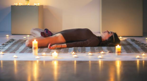 Relaxation time: a woman practises yoga by candlelight
