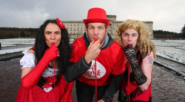 Ulster Rugby player Chris Henry (centre) launches the the Red Dress Run with the first two entrants Gillian Abraham (left) and Graham Ross
