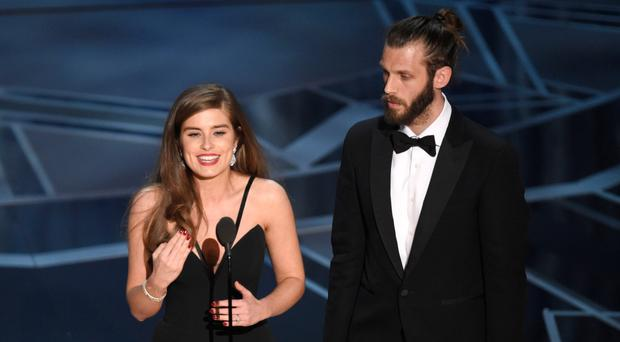 Big winners: Rachel Shenton signs as she and fiance Chris Overton accept the Oscar for The Silent Child