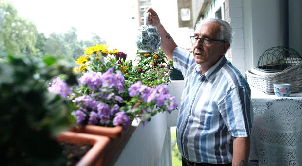 Resident John Leitch waters his plants