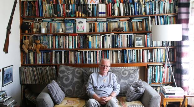 Journalist and author Colin McAlpin relaxes at home with his vast book collection