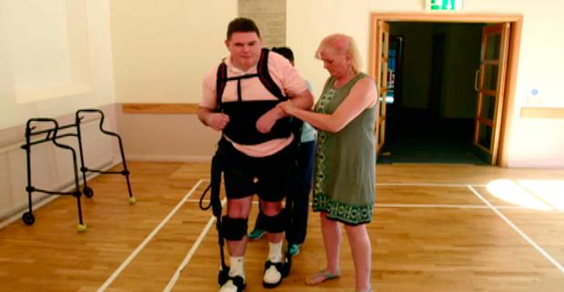 Stephen using the exoskeleton with his sister Yvonne