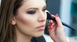 A woman adds blusher