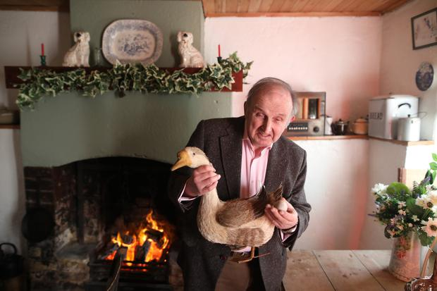Creighton Hutchinson in front of the open hearth in Rosie's Cottage