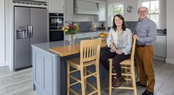 Tim and Mairead Andrew in the grey hand-painted kitchen with units by Hannaway Hilltown Kitchens