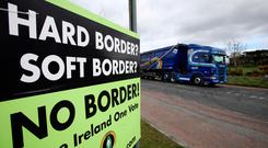 Clear message: a lorry passes a poster calling for 'No Border' between Ireland and Northern Ireland