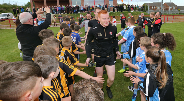 Derry GAA football star Conor McAtamney is mobbed as the team take to the pitch at Sean Dolan's