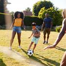 Outdoor games: a family enjoys playing football