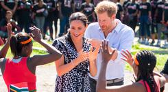 On the road: the Duke and Duchess of Sussex meet a group of dancers in Cape Town, South Africa, where they are travelling with their son
