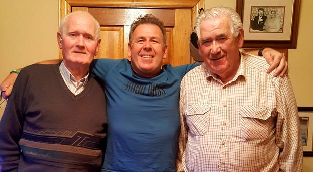 Modest men: (from left) Michael, Jim and James Gallagher at home in Burtonport, Co Donegal, with a photo of their boat, Irine