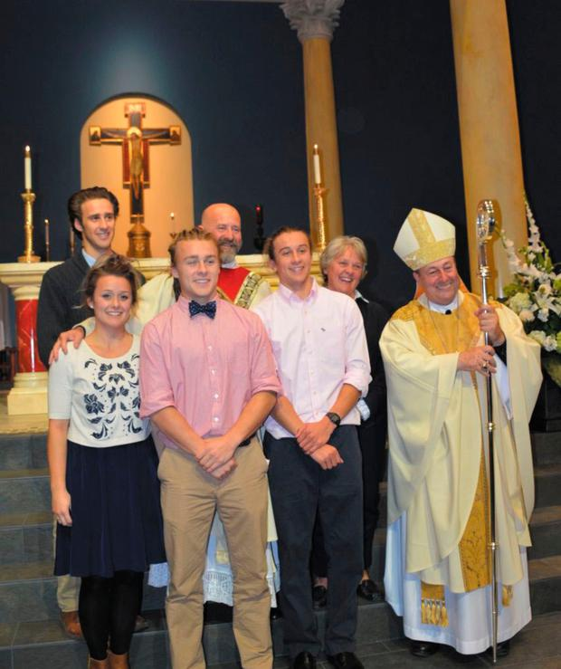 New direction: Father Dwight Longenecker (fourth left) and his wife and four children at the dedication of the new Our Lady of the Rosary Church by Bishop Robert Guglielmone (right) in South Carolina