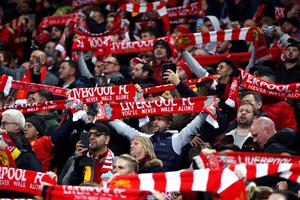 Fans with scarves aloft at Anfield