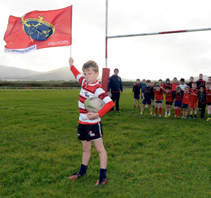Flying the flag: Harry Curran proudly waves the Munster colours in front of trainers and some of the young members of Dingle Rugby Club in Corrig, west Kerry