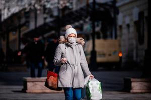 Facts and figures: a masked woman carries home her supplies of toilet paper