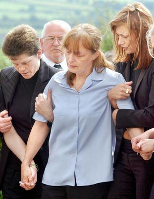 Unanswered questions: Mavis McFaul is comforted at the 2002 funeral of partner David Caldwell, whose family is still asking for a full inquiry into his death