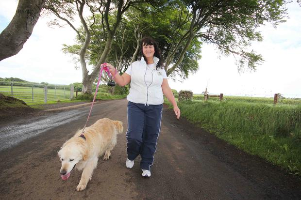 Location, location: Sheila Elliott, from Stranocum, walks her dog Sasha along the road at the Dark Hedges