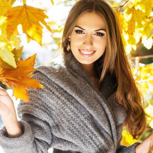 Young fashion girl wearing warm knitted coat in autumn park