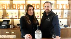 Fiona Boyd-Armstrong and her husband David in the Crossgar distillery with a bottle of their Shortcross gin