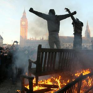 Two demonstrators stand by a bonfire in Parliament Square