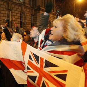 Loyalist protestors carrying Union flags block the back of the City Hall in Belfast