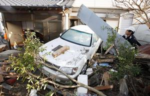 A resident of the seaside town of Yotsukura, northern Japan, clears debris from his home Monday, March 14, 2011, three days after a giant quake and tsunami struck the country's northeastern coast. (AP Photo/Mark Baker)