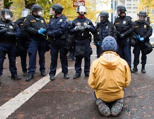 PORTLAND - NOVEMBER 13: A protester sits in the street in defiance of police orders near the Occupy Portland encampment November 13, 2011 in Portland, Oregon. Portland police have reclaimed the two parks in which occupiers have been camping after a night of brinksmanship with protesting crowds of several thousands. (Photo by Natalie Behring/Getty Images)